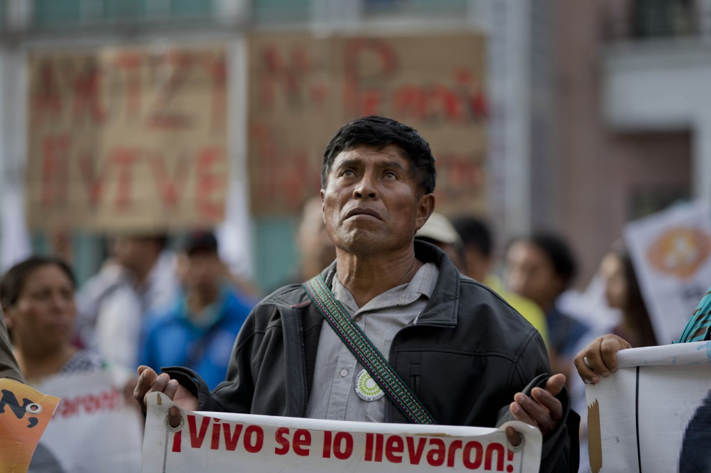 "A demonstrator carries a sign that reads in Spanish: ""They took them alive, return them alive,"" in reference to 43 missing students from the Ayotzinapa rural teachers college, during a march to the private TV channel Televisa in Mexico City, Tuesday, March 10, 2015. The missing students' parents and supporters accuse national media outlets of decreasing their coverage of the missing students after statements by then-Attorney General Jesus Murillo Karam who said his investigators indicated all 43 students were killed by the Guerreros Unidos drug gang. The parents still have no concrete information on what happened to their children, and demand their voices be aired in order to continue the search for them. (AP Photo/Eduardo Verdugo)"